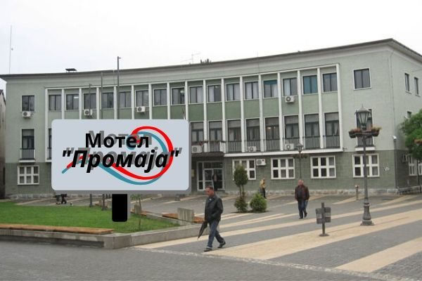 Slika zgrade opštine Požega sa transparentom ispred na kome piše motel promaja