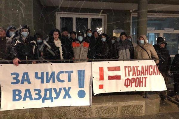 Ljudi stoje u grupi ispred opštine držeći parole